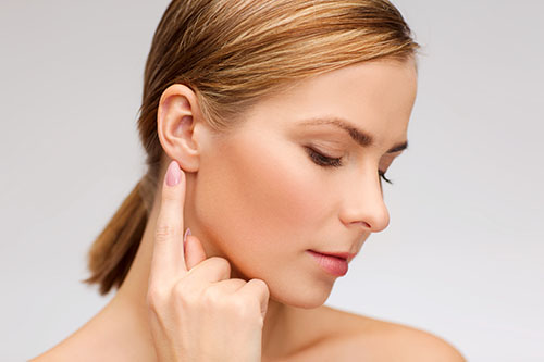 Woman pointing to her ear