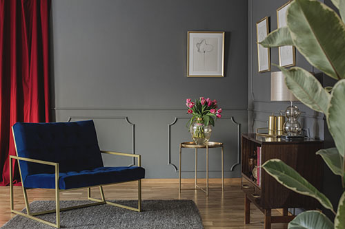 Navy blue armchair next to gold table with pink flowers